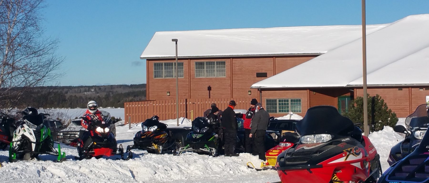 snowmobiles lined up in font of Grand Ely Lodge