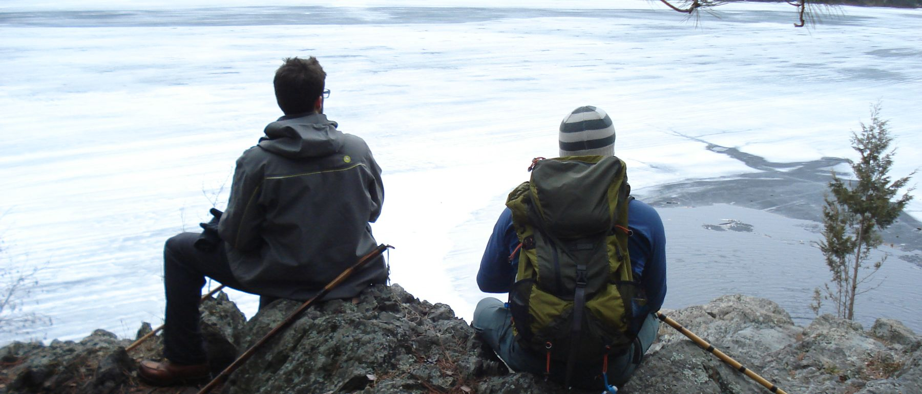 Hikers looking at scenic frozen pond near Grand Ely Lodge