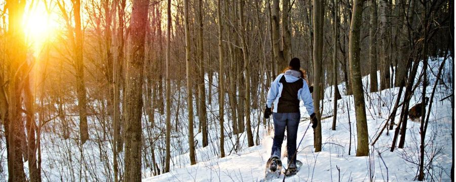woman trekking through the snow with snow shoes at Grand Ely Lodge in Minnesota